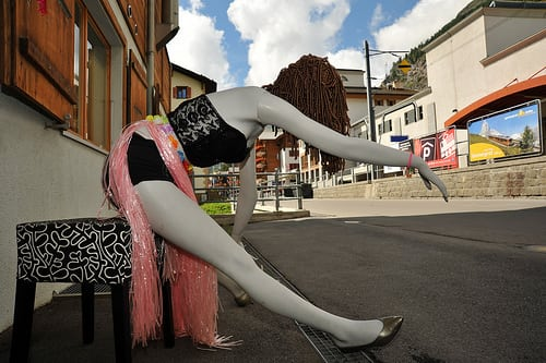 Store front of a hair dressing shop shows a mannequin in a radical pose intended to draw lady patrons to their store who will want a makeover and pay for the service (How Do I Look?).…